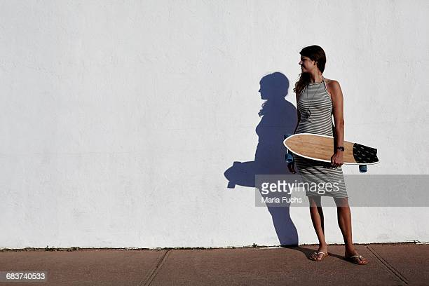 Cool young woman standing in front of white wall holding skateboard, New York, USA