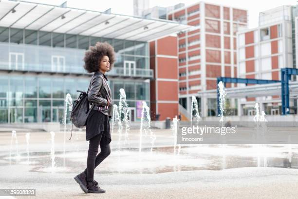 cool young woman with afro hair on city concourse, full length - black trousers stock pictures, royalty-free photos & images