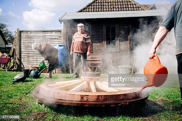 Cooling the metal tyre onto a wooden cartwheel, traditional wheelwrights