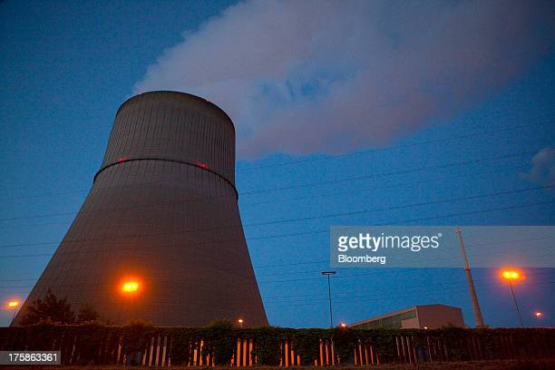 A cooling tower emits vapor into the night sky as power transmission lines are seen at a nuclear power plant operated by RWE AG in Emsland Germany on...