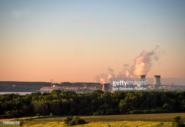 cooling towers at nuclear power station against sky during sunset - atomic imagery fotografías e imágenes de stock
