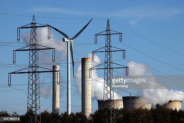 Cooling towers operate behind electrity pylons and a wind turbine at the RWE AG coalfueled power plant in Weisweiler Germany on Sunday Oct 3 2010...