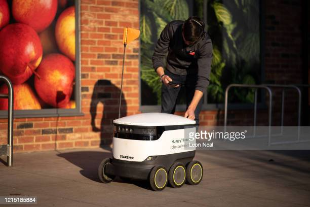 Co-op food store employee loads an order into a delivery robot before it negotiates the empty pavements and pathways to make a home delivery on March...