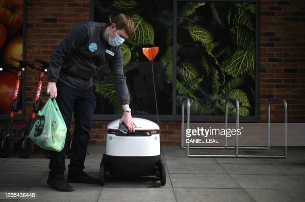 Co-op grocery store worker loads a bag inside an autonomous robot called Starship prior to its delivering groceries in Milton Keynes, England on...