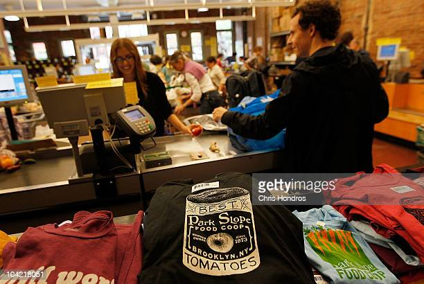 A coop shopper bags his groceries near promotional Tshirts while a fellow coop member works the cash register at the the Park Slope Food Coop on...