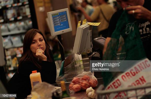A coop shopper bags his groceries while a fellow coop member works the cash register at the Park Slope Food Coop on September 17 2010 in the Brooklyn...