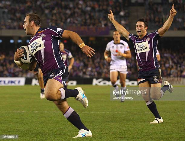 Cooper Cronk celebrates as Ryan Tandy of the Storm scores a try during the round seven NRL match between the Melbourne Storm and the Warriors at...