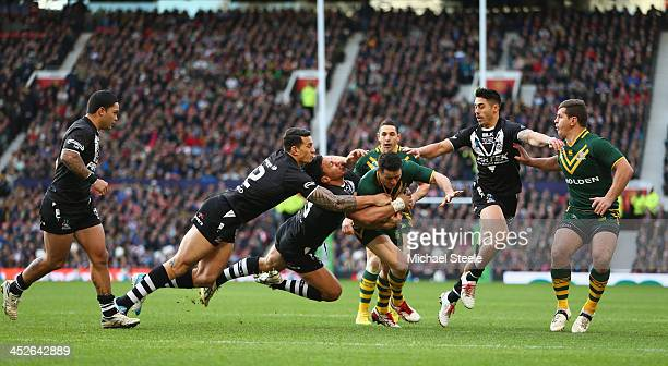 Cooper Cronk of Australia is held up by Dean Whare and Sonny Bill Williams of New Zealand during the Rugby League World Cup Final between Australia...