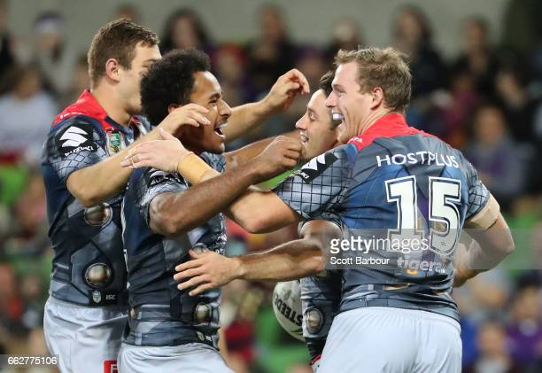 Cooper Cronk of the Melbourne Storm is congratulated by his teammates after scoring a try during the round five NRL match between the Melbourne Storm...
