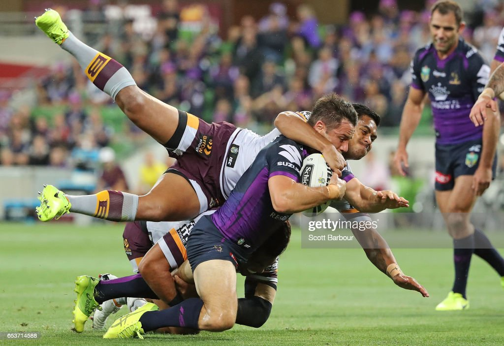 Cooper Cronk of the Melbourne Storm is tackled by Anthony Milford of the Broncos and falls just short of the try line during the round three NRL match between the Melbourne Storm and the Brisbane Broncos at AAMI Park on March 16, 2017 in Melbourne, Australia.