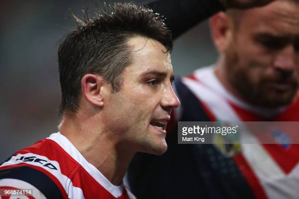Cooper Cronk of the Roosters talks to team mates during the round 13 NRL match between the Sydney Roosters and the Wests Tigers at Allianz Stadium on...