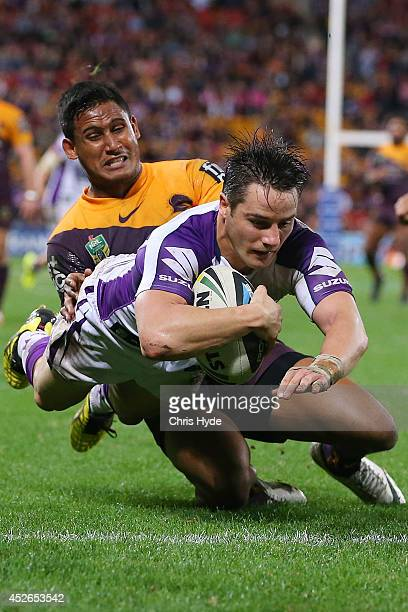 Cooper Cronk of the Storm dives to score a try while tackled by Ben Barba of the Broncos during the round 20 NRL match between the Brisbane Broncos...