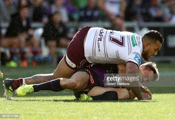 Cooper Cronk of the Storm is challenged by Addin FonuaBlake of the Sea Eagles during the round 21 NRL match between the Melbourne Storm and the Manly...