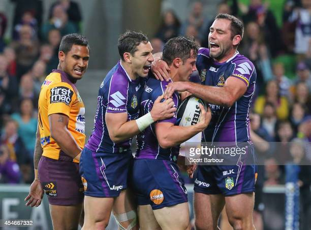 Cooper Cronk of the Storm is congratulated by Cameron Smith and Billy Slater after scoring a try during the round 26 NRL match between the Melbourne...