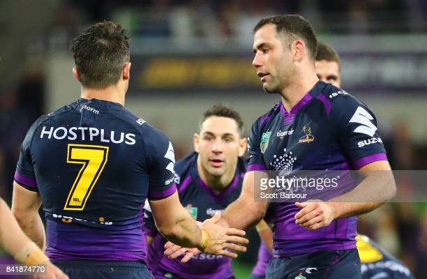 Cooper Cronk of the Storm is congratulated by Cameron Smith and Billy Slater after he played his final home match after the round 26 NRL match...