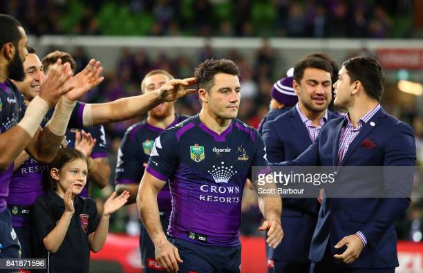 Cooper Cronk of the Storm is congratulated by his teammates after he played his final home match after the round 26 NRL match between the Melbourne...