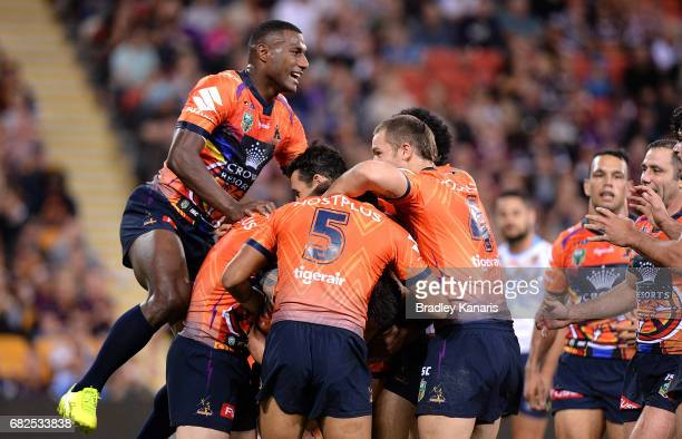 Cooper Cronk of the Storm is congratulated by team mates after scoring a try during the round 10 NRL match between the Melbourne Storm and the Gold...