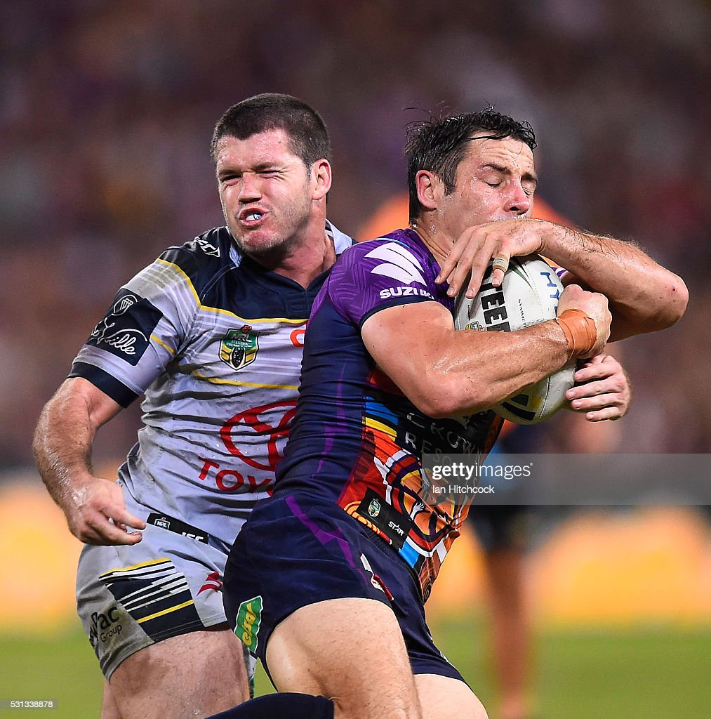 Cooper Cronk of the Storm is tackled by Lachlan Coote of the Cowboys during the round 10 NRL match between the Melbourne Storm and the North Queensland Cowboys at Suncorp Stadium on May 14, 2016 in Brisbane, Australia.