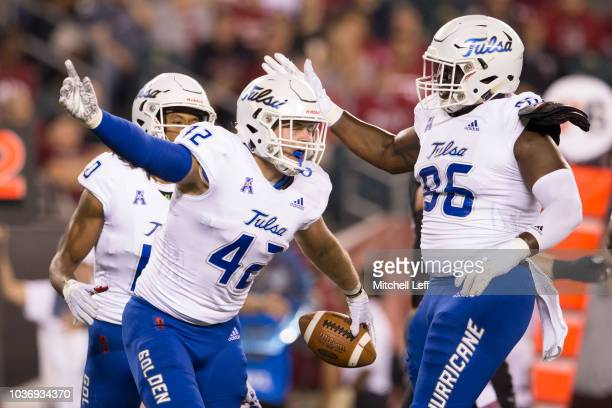 Cooper Edmiston of the Tulsa Golden Hurricane reacts along with Myles Mouton after intercepting a pass in the first quarter against the Temple Owls...