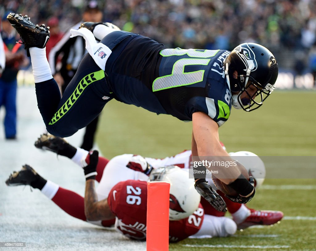 Cooper Helfet #84 of the Seattle Seahawks dives to score a 20 yard touchdown passed by Russell Wilson #3 in the third quarter against the Arizona Cardinals during their game at CenturyLink Field on November 23, 2014 in Seattle, Washington.