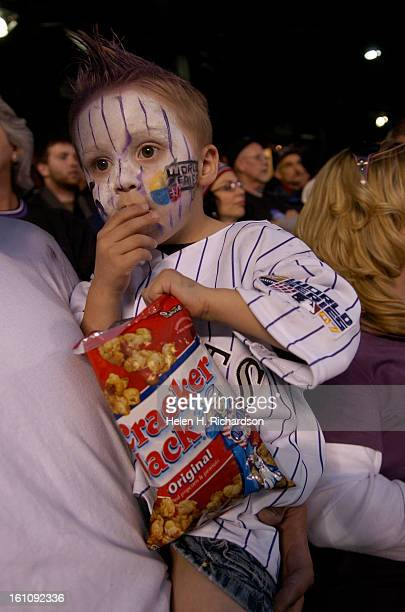 Cooper Hertz of Breckridge, digs in to a package of Cracker Jacks prior to the start of game four of the World Series between the Colorado Rockies...