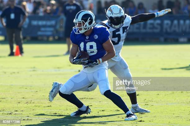 Cooper Kupp of the Los Angeles Rams runs the ball down field while being defended by Jatavis Brown of the Los Angeles Chargers during a combined...