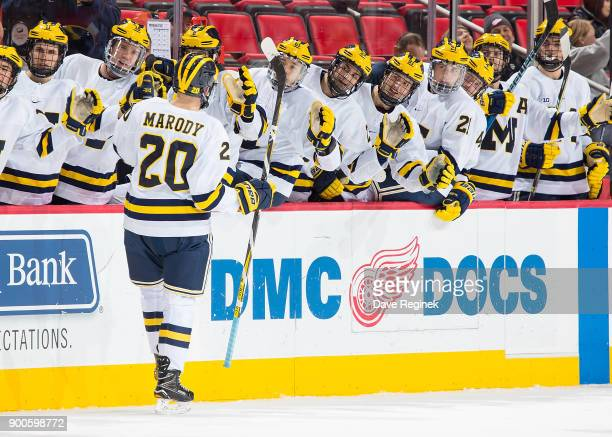 Cooper Marody of the Michigan Wolverines celebrates a goal with teammates on the bench after his third period hat trick goal against the Michigan...