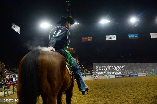 Cooper Martin of Alma KS Tanner Green of Cotulla TX wipes off talcum powder on he used for his hands and rope on the back of his horse as he gets...