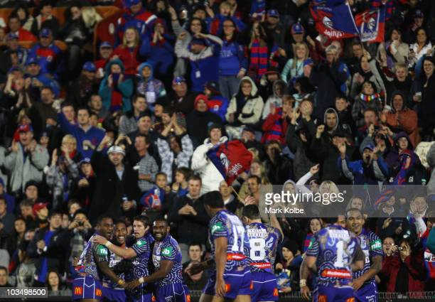 Cooper Vuna of the Knights is congratulated by his team mates after scoring a try during the round 24 NRL match between the Newcastle Knights and the...