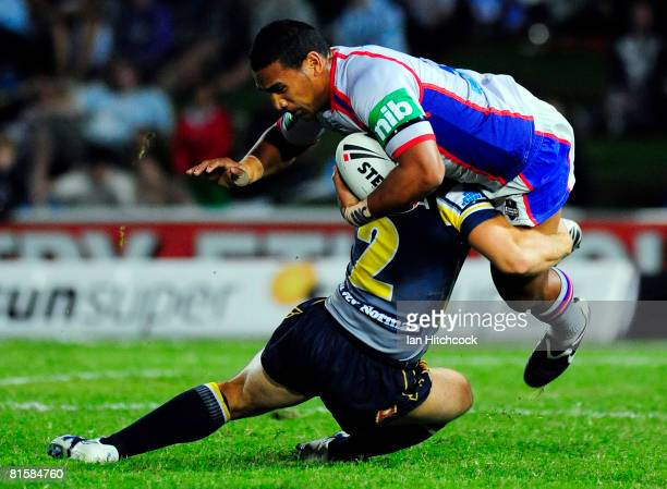 Cooper Vuna of the Knights is tackled by Mark Henry of the Cowboys during the round 14 NRL match between the North Queensland Cowboys and the...
