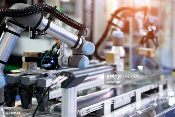 co-operate robot is working by pick the box to packing in manufacturing factory concept smart warehouse 4.0. - fabricage apparatuur stockfoto's en -beelden