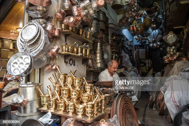 A coopersmith works at his workshop at the historical Antakya bazaar on June 5 2017 in Hatay / AFP PHOTO / OZAN KOSE