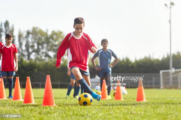 coordinated young footballer completing dribbling drill - sports training drill stock pictures, royalty-free photos & images