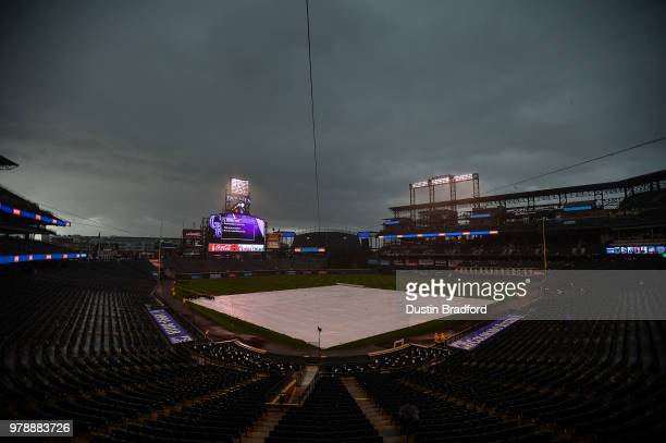 Coors Field is covered with a tarp as rain falls in the area and a tornado watch is in effect during a rain delay before a potential game between the...
