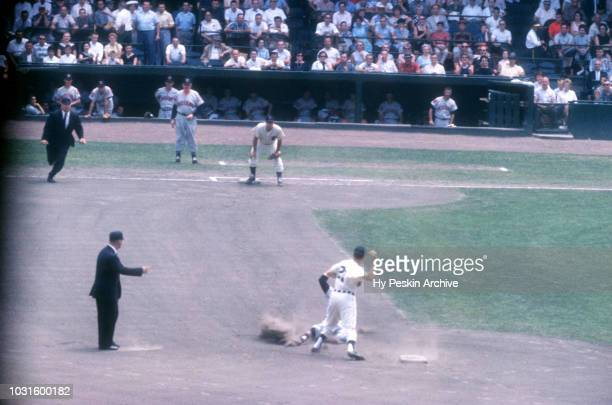 Coot Veal of the Detroit Tigers gets ready to throw to his teammate Bobo Osborne to complete the double play as George Strickland of the Cleveland...