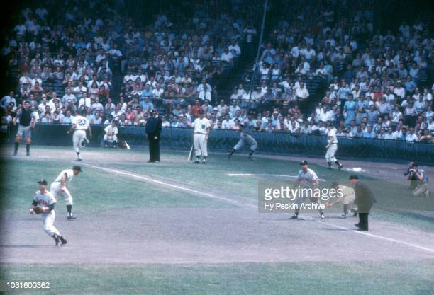 Coot Veal of the Detroit Tigers scores as teammate Eddie Yost gets ready to slide while third baseman Granny Hamner of the Cleveland Indians waits...
