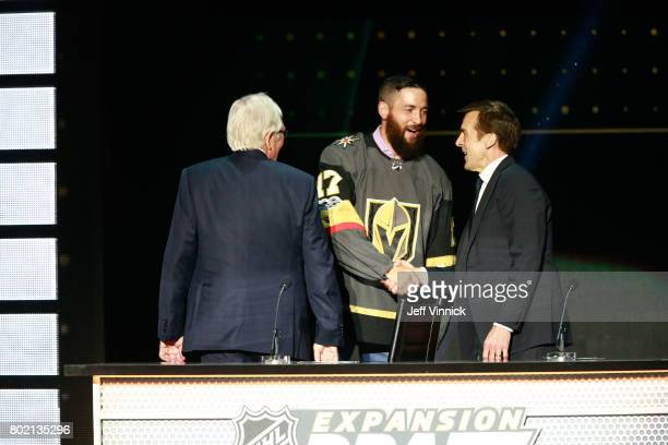 Coowner Bill Foley and general manager George McPhee of the Vegas Golden Knights greet defenseman Deryk Engelland onstage during the 2017 NHL Awards...
