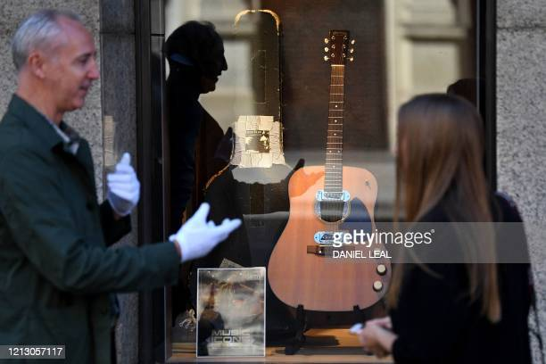Coowner of Julien's Auctions Martin Nolan chats to a passerby about the guitar used by musician Kurt Cobain during Nirvana's famous MTV Unplugged in...
