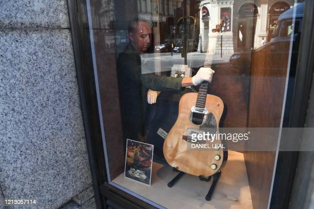 Coowner of Julien's Auctions Martin Nolan places the guitar used by musician Kurt Cobain during Nirvana's famous MTV Unplugged in New York concert in...