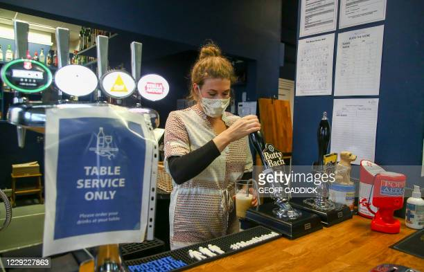 Co-owner of the Banc pub, Holly Adams-Evans, works behind the bar in Knighton, a town which sits on the border of England and Wales, on October 21,...