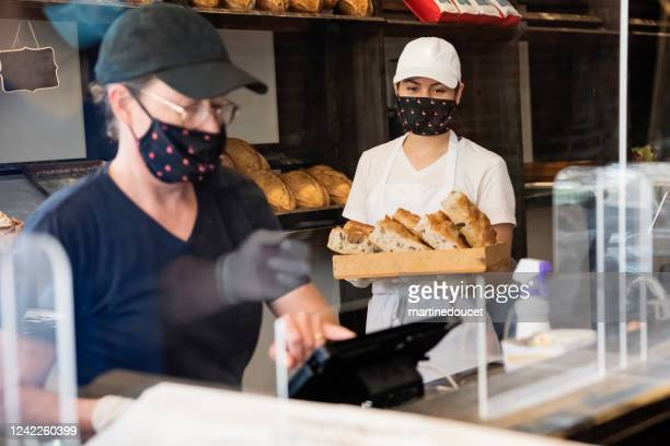 """co-owners of bakery shop working wearing masks. - """"martine doucet"""" or martinedoucet stock pictures, royalty-free photos & images"""
