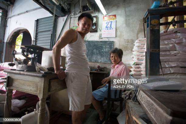 Co-owners Zheng Jing-Xiu and sister Zheng Yu Yan pose in the Hsing Qin Li Rice Mill in Dadaocheng, Taipei on July 28, 2018. - The mill, which is the...