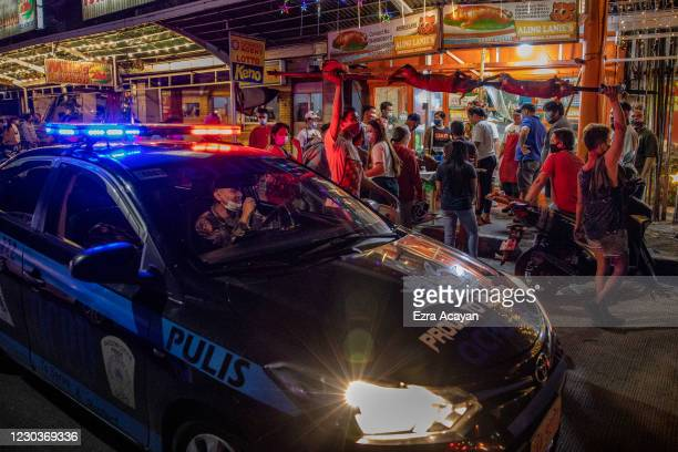 """Cop in a police mobile uses a speaker to remind Filipinos to observe social distancing as they queue to buy roasted pigs known locally as """"lechon"""", a..."""