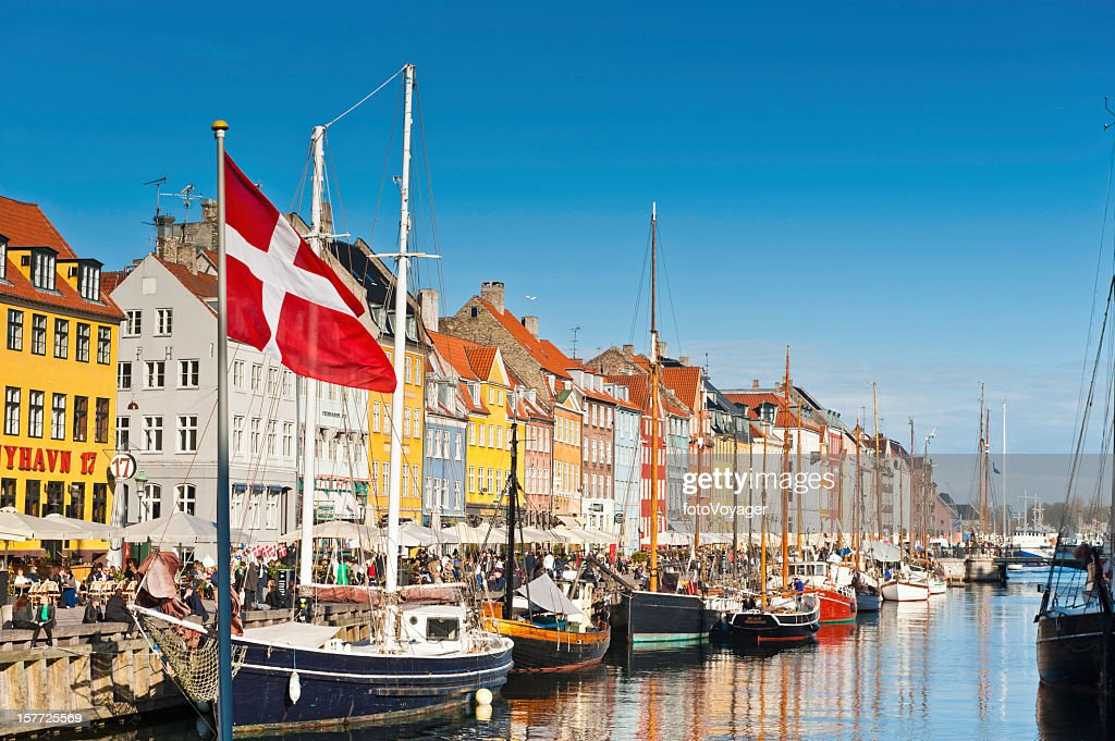 Copenhagen Danish flag flying over Nyhavn colourful harbour : Stock Photo