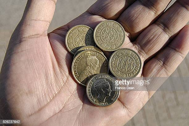 Copenhagen / Denmark _Danish money kroner coins on hand palm and danish economy coins with portrait of danosh Queen HMThe Queen Margrethe II 11 July...