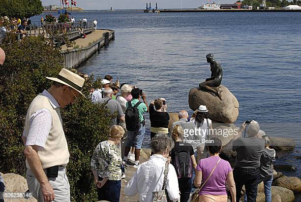Copenhagen / Denmark _Tourists are watching and photographing to Little Mermaid at langeline 31 July 2013