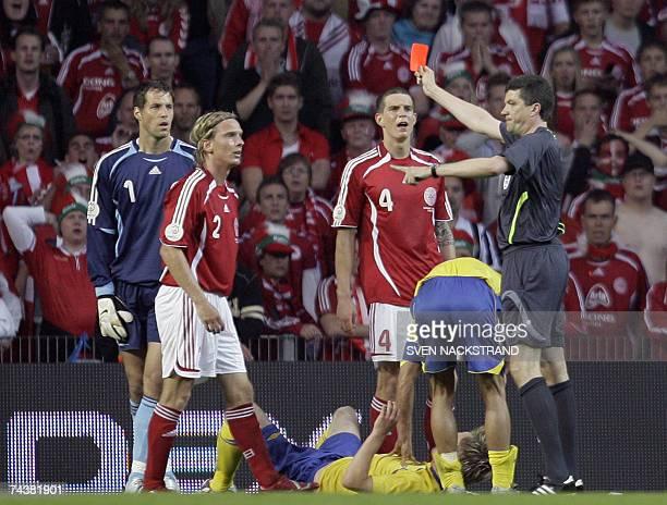 Danish defender Christian Poulsen is handed a red card by German referee Herbert Fandel after he tackled Sweden's Markus Rosenberg during their...