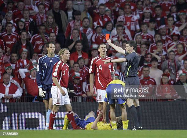 Danish defender Christian Poulsen is handed a red card by German referee Herbert Fandel after a punch in the stomach on Sweden's Markus Rosenberg...