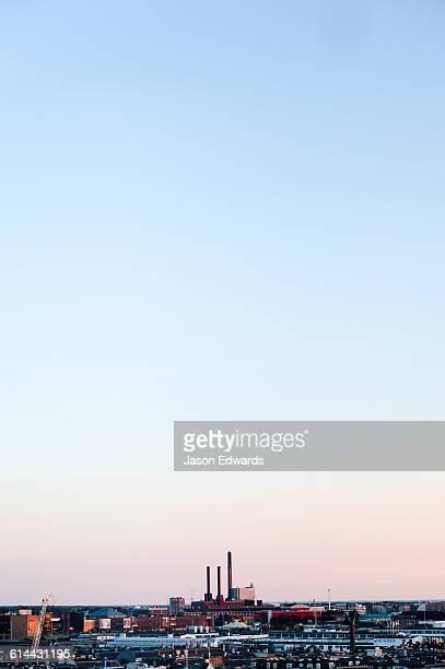 Factory chimneys rise above the flat city skyline of Copenhagen at sunset.