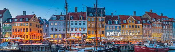 Copenhagen Nyhavn colorful bars and restaurants illuminated at dusk Denmark